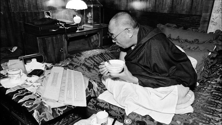 His Holiness the Dalai Lama reading Buddhist texts as he eats breakfast at his residence in Dharamsala, HP, India on 15 August, 2004. (Photo courtesy of Manuel Bauer)